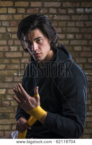 Young Malaysian boxer  wearing hoodie and wrapping straps around hands