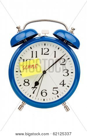 an alarm clock with a sticky note: