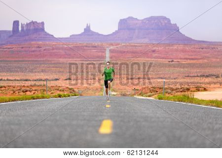 Running man - runner sprinting on road by Monument Valley. Concept with sprinting fast training for success. Fit sports fitness model working out in amazing landscape nature. Arizona, Utah, USA.