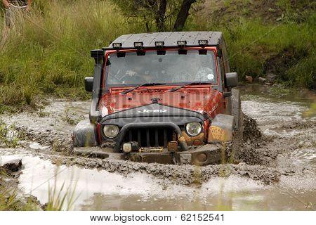 Crush Orange Jeep Rubicon Crossing Muddy Pond