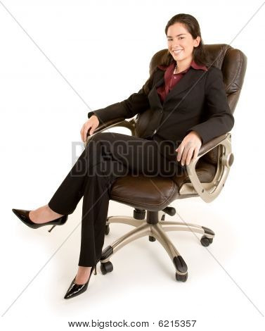 Smiling Businesswoman Sitting On A Leather Chair
