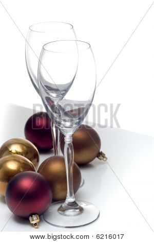 Champagne glasses beside christmas ornaments