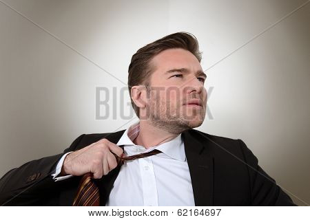 Young businessman loosening a tie