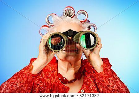 Portrait of an elderly woman in curlers looking ahead through binoculars.