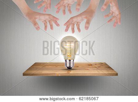 Bulb on wood shelf with hand