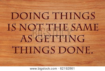 Doing things is not the same as getting things done - on wooden red oak background poster