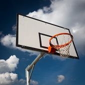 Basketball hoop against  lovely blue summer sky with some fluffy white clouds poster