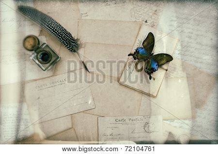 old letters handwritings vintage postcards and antique feather pen. nostalgic sentimental background with butterfly. retro style toned picture poster