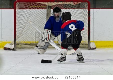 Young ice hockey player prepares to shoot on net poster