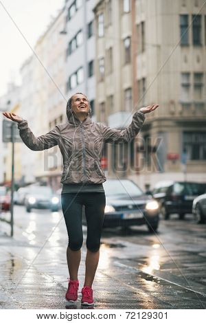 Full Length Portrait Of Happy Fitness Young Woman Catching Rain