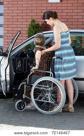 Girl Assisting Disabled Woman Getting Into A Car