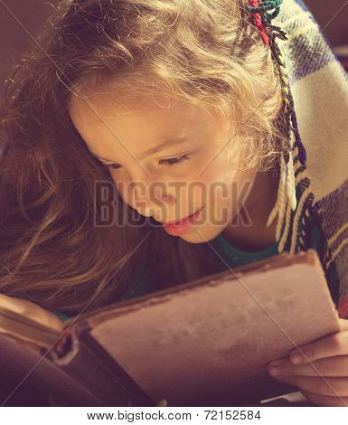 Vintage portrait of Young curly school girl reading a book