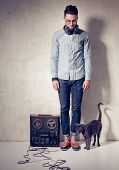 handsome man and cat listening to music on a magnetophone against grunge wall poster
