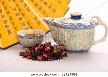 Mystery of tea ceremony. Closeup image of the heap of colored tealeaves placed in front of traditional crockery and Chinese hand fan with hieroglyphs isolated on white background poster