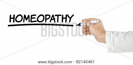 Hand with pen writing Homeopathy on a white background