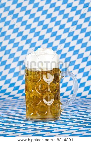 Oktoberfest beer stein and Bavarian flag in background.