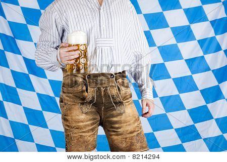 Bavarian man with leather pants (Lederhose) holds Oktoberfest beer stein (Mass).