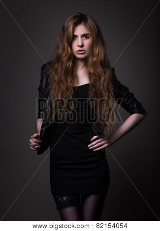 Attractive Woman In Black Dress And Leather Jacket