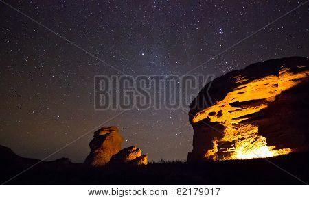 bounfire lights big rock with sitting man