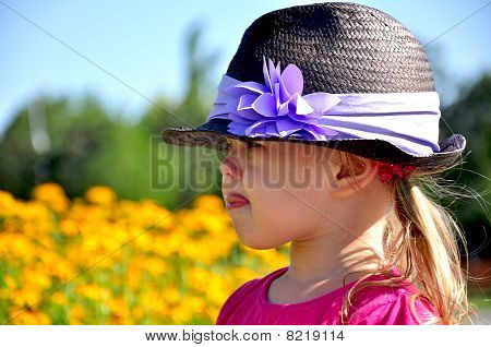 Portrait of cute little girl showing a tongue in the park
