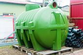 huge green plastic septic tank standing on a pallet poster