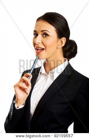 Pensive businesswoman holding a pen under chin.