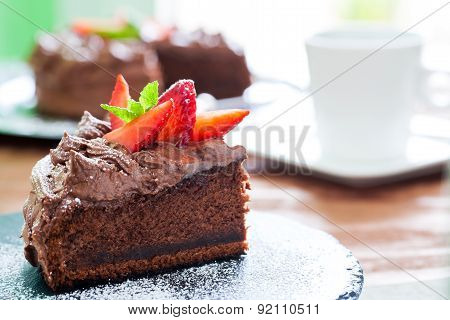 Slice Of Chocolate Cake With Coffee In Background.