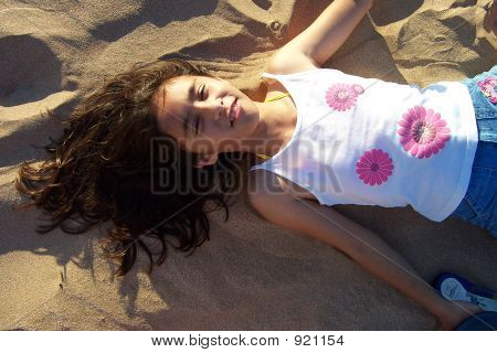 Pretty Girl Laying On The Sand At The Beach
