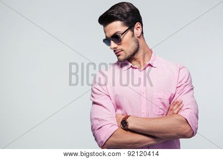 Fashion young man in glasses standing with arms folded over gray background and looking away