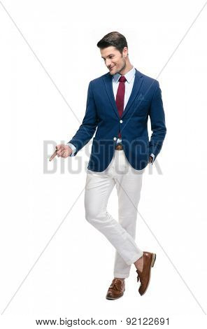 Full length portrait of a confident businessman pointing finger down isolated on a white background