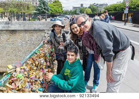 Family Locking Love Padlock At Seine Bridge In Paris, France