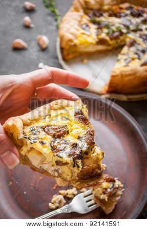 Woman's Hand Holding A Caramelized Garlic Tart With Goat Cheese And Herbs