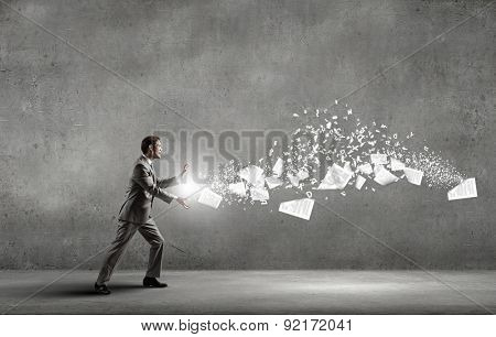 Businessman controlling paper documents flying in air
