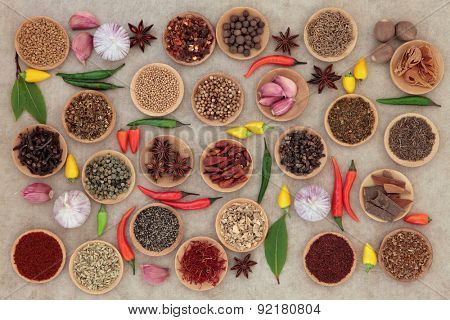 Herb and spice collection in wooden bowls and loose over old grunge paper background.