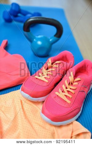Gym shoes - Fitness outfit closeup with kettlebell. Crossfit workout clothes on yoga mat in pink neon color with weights in the background on the floor. Fashion activewear clothes concept.