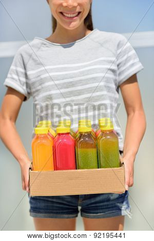Juice detox - cleanse diet with juicing raw and organic fruits and veggies. Fresh juices delivery woman with vegetable drinks. Young girl carrying a box of juice bottles. poster