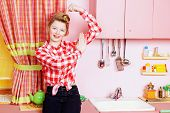 Pretty girl teenager wearing clothes and hair in pin-up style posing on a pink kitchen. Beauty, youth fashion. Pin-up style. poster