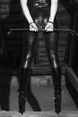 Sexy woman body in latex catsuit dominatrix holding whip in barn black and white bdsm poster