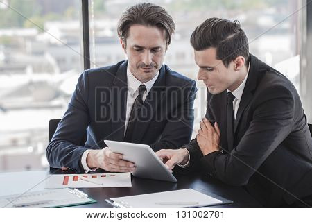 Business people discussing the charts and graphs showing the results of their successful teamwork