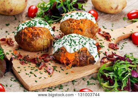 Hot Baked Potato with cheese, bacon, chives and sour cream. on cutting board