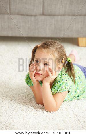 Porträt von kleinen Mädchen auf Boden zu Hause liegen wegsehen.