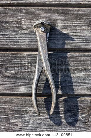 shabby rusty metal pliers (wire cutter) with red handles hanging on wooden board wall closeup