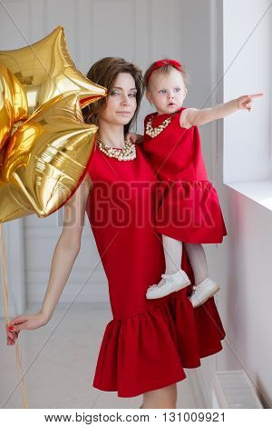 Portrait of mother with little daughter on a light gray background in the Studio with balloons,mom-brunette with long curly hair and gray eyes and a little girl with short hair,a red bow on his head,both dressed in red dresses and pearl necklaces