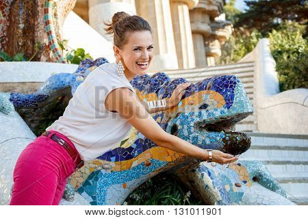 Smiling Woman Near Mosaic Dragon In Park Guell, Spain