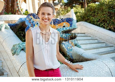 Portrait Of Happy Woman Near Mosaic Dragon In Park Guell, Spain