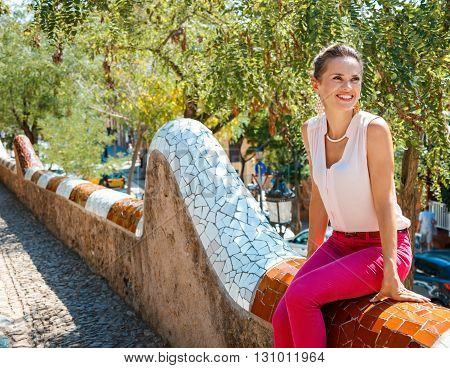 Happy Woman Sitting On Trencadis Style Fence And Looking Aside