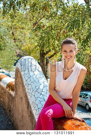 Portrait Of Happy Young Woman Sitting On Trencadis Style Fence