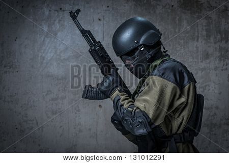 Terrorist soldier in a camouflage and helmet with rifle poster