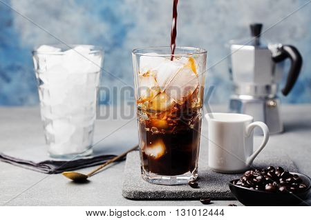 Ice coffee in a tall glass and coffee beans on a grey stone background poster