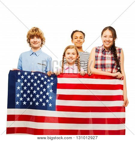 Four happy multiethnic teenage kids holding the star-spangled banner, isolated on white
